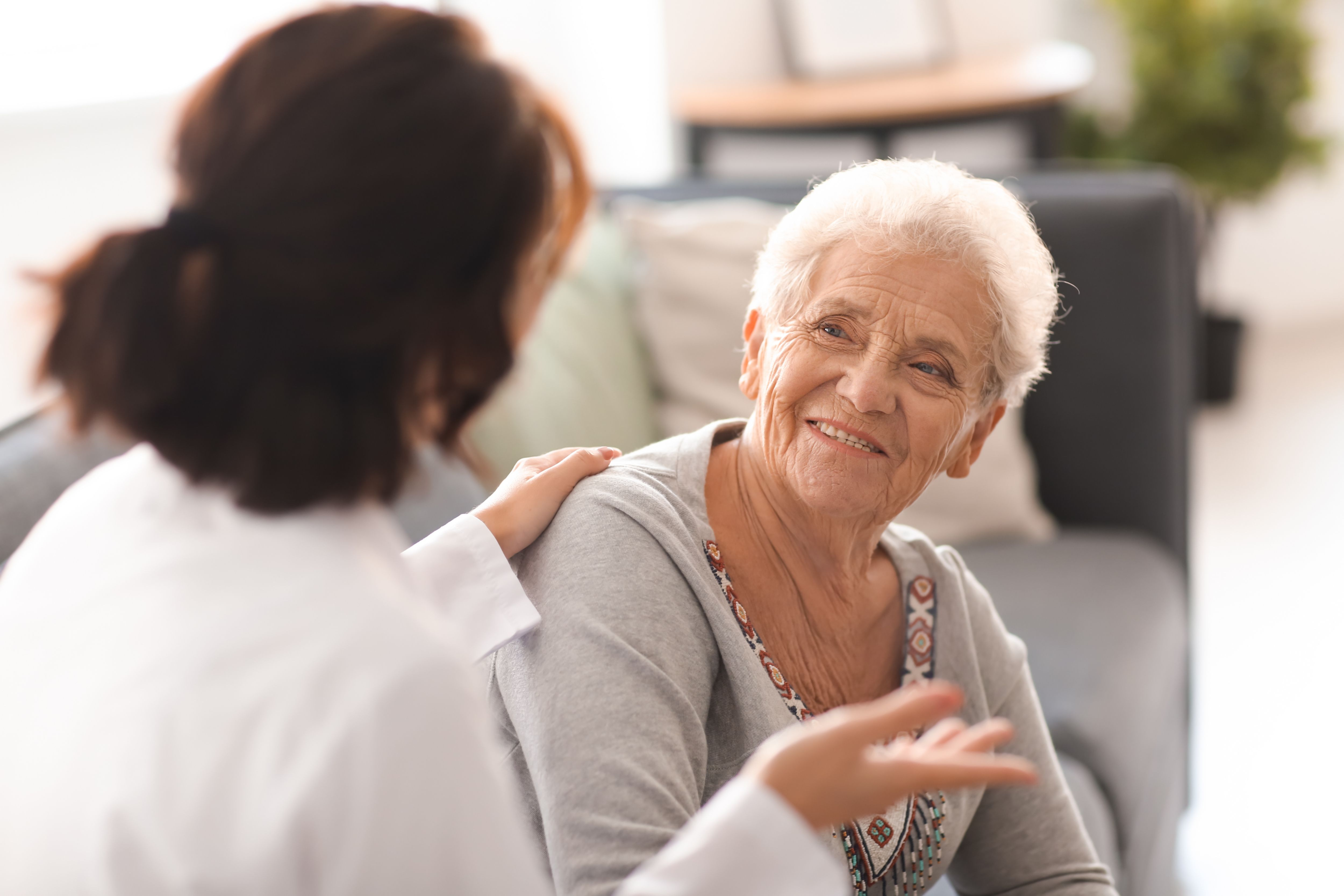 Young doctor visiting elderly woman at home