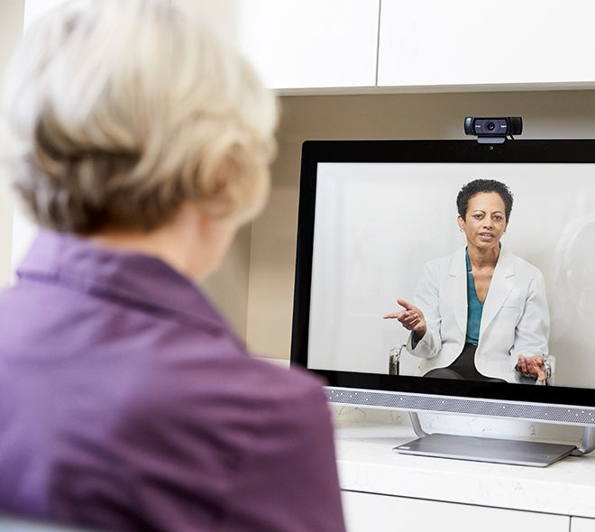 Senior receiving virtual care from her doctor via televisit on her computer