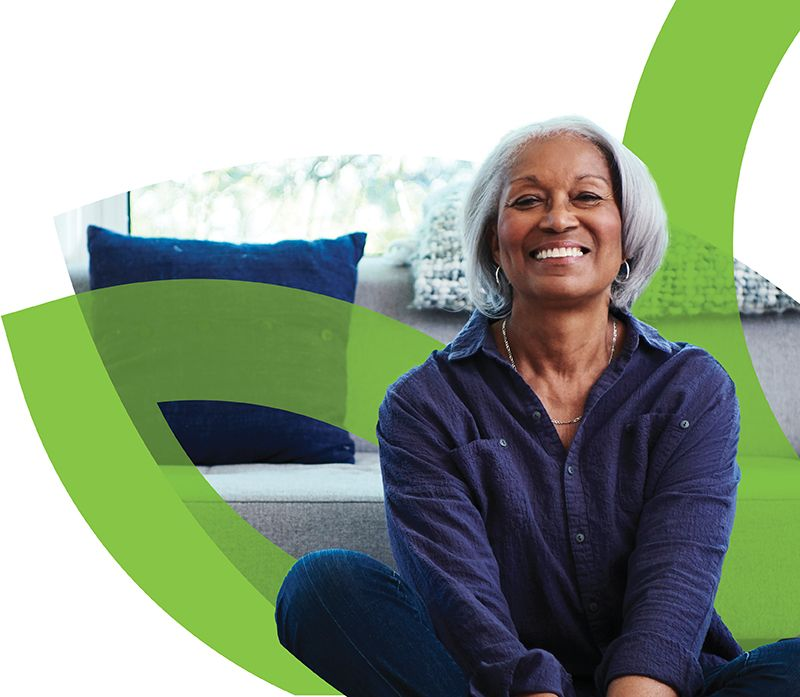 test Woman smiling while sitting cross-legged in front of CenterWell logo