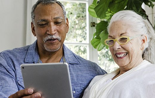 Elderly man and woman looking at iPad tablet together exploring the CenterWell health portal