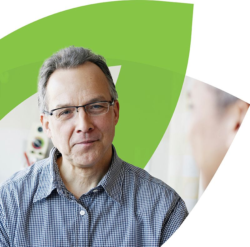 Man with glasses in front of CenterWell logo