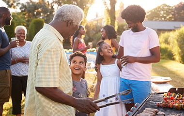 Black grandfather cooking on the barbeque outside with his family