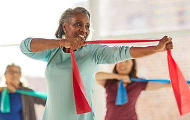 Elderly black woman exercising in class with a red resistance band