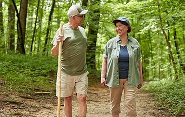 Elderly husband and wife smiling while walking in nature