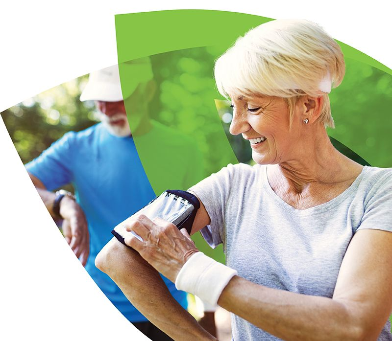 Senior woman in exercise gear using her phone strapped to her arm