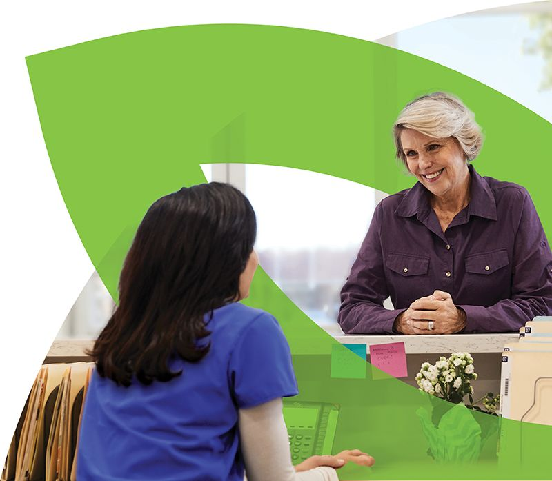 Senior woman speaking with receptionist at doctor's office in front of CenterWell logo