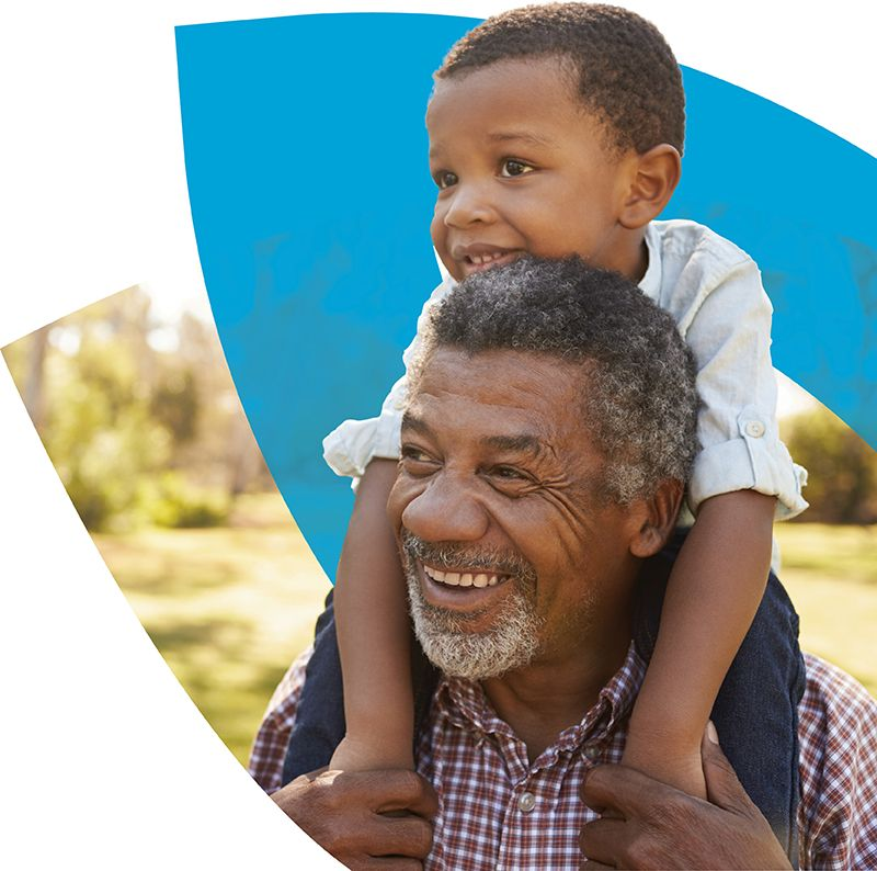 Elderly man carrying his grandchild on his shoulders in front of the CenterWell logo