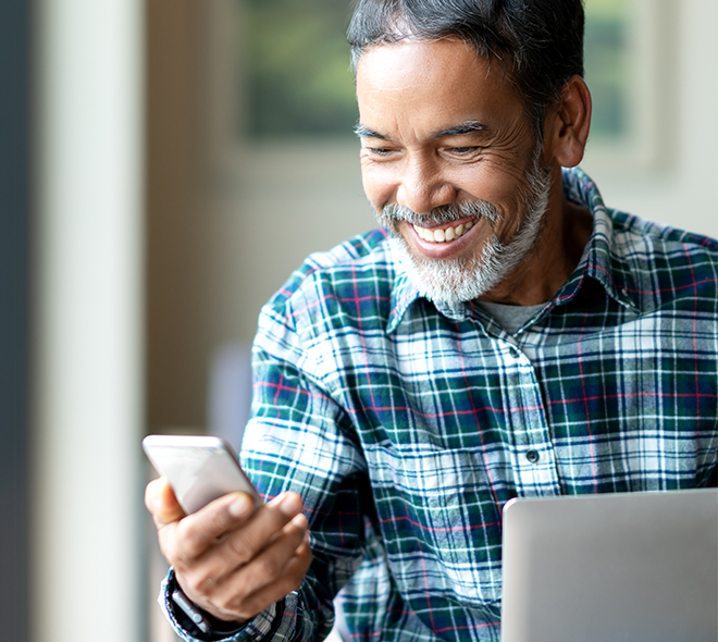 Elderly black man smiling and looking at his phone
