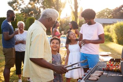 Grandad and grandson talk by the grill at a family barbecue