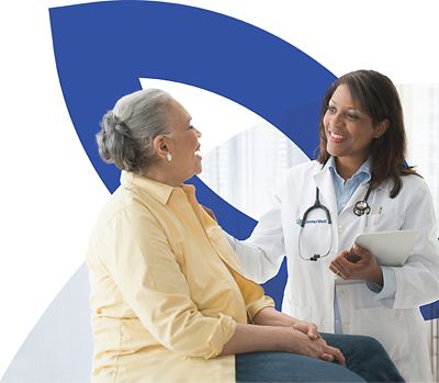 Female doctor talking to seated patient in front of CenterWell logo